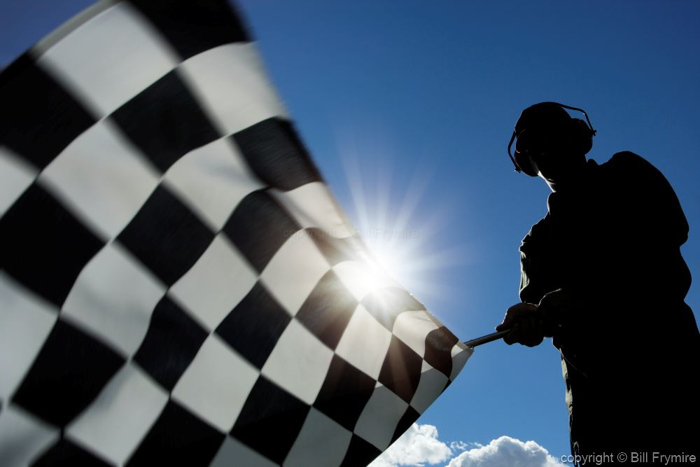 man waving checkered flag - model released - low angle